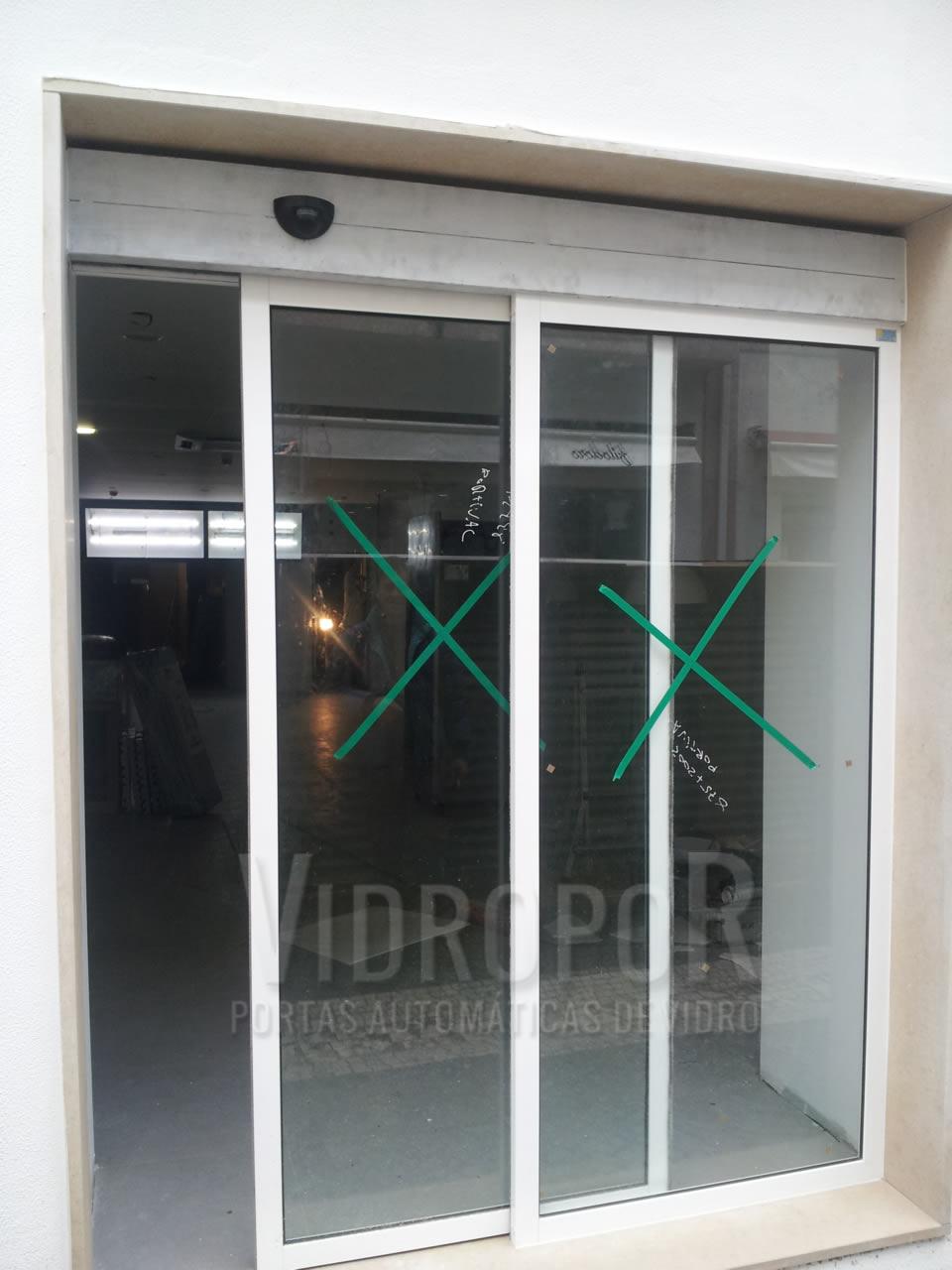 Porta automática de vidro perfis cor branco com sistema anti-entalamento.